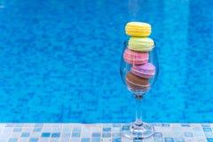 在玻璃酒的甜和五颜六色的法国蛋白杏仁饼干与蓝色col 免版税图库摄影