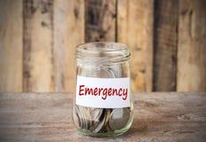 在玻璃金钱瓶子的硬币有紧急标签的,财政概念 库存照片