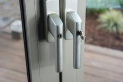 在玻璃门的锁对作为防御的庭院闯入的 库存图片