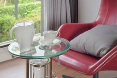 在玻璃顶面桌上的茶具与在客厅内部的红色安乐椅 库存照片
