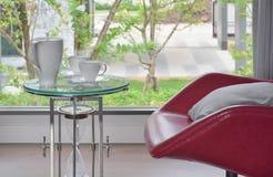 在玻璃顶面桌上的茶具与红色安乐椅在客厅 库存照片