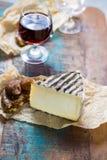 在玻璃,干法国乳酪Tomme de的甜点心利口葡萄酒 免版税图库摄影