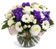 在玻璃,透明花瓶的花卉构成:白玫瑰,紫罗兰色兰花,白色大丁草雏菊,绿豆。隔绝在白色。 免版税库存图片