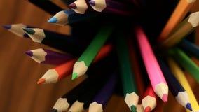 在黑玻璃移动的许多多彩多姿的铅笔在黑木背景的一个圈子 概念办公室或学校,知识天, 影视素材