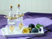 在玻璃玻璃水瓶的传统李子白兰地酒 在背景的新鲜的李子 库存图片