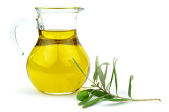 在玻璃玻璃水瓶的橄榄油和绿橄榄分支 免版税库存照片