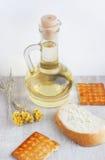 在玻璃水罐、曲奇饼、切片面包和fl的向日葵种子油 图库摄影