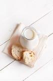 在玻璃水罐和面包的牛奶 免版税库存图片