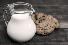 在玻璃水罐和饼干的牛奶 库存照片