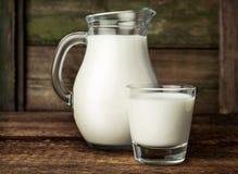 在玻璃水罐和玻璃的新鲜的牛奶 库存图片