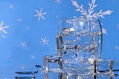 在玻璃- BlueSnowflake背景的冰块 库存图片
