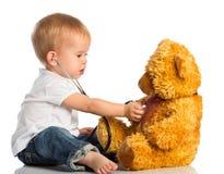 在医生玩具熊和听诊器的婴孩戏剧 库存图片