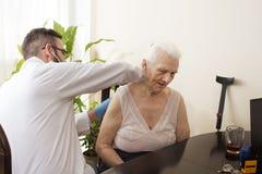 在医生` s办公室篡改审查有一个听诊器的一个老妇人 免版税库存照片