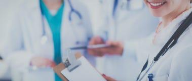 在医疗小组前面的可爱的女性医生 免版税图库摄影