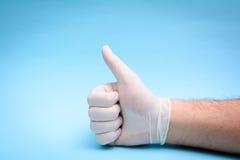 在医疗手套的手在蓝色背景 免版税图库摄影