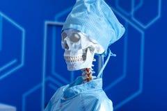 在医疗晨衣的人的骨骼在蓝色bacground 库存照片