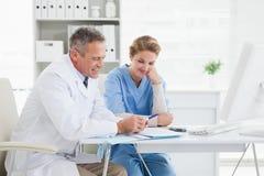 读在医疗笔记的医生和护士 图库摄影