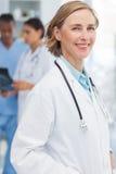 在医疗队前面的微笑的妇女医生 免版税库存照片