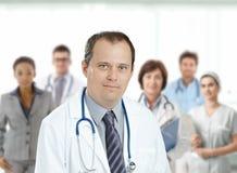 在医疗队前面的确信的男性医生 免版税库存照片