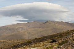 在贫瘠倾斜上的双突透镜的云彩 免版税库存照片