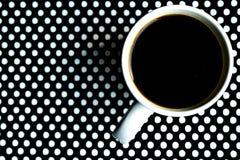 在黑白圆点背景的咖啡杯 库存图片