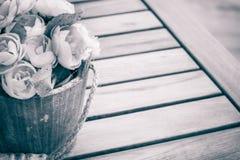 在黑白木的桌上的花 库存图片