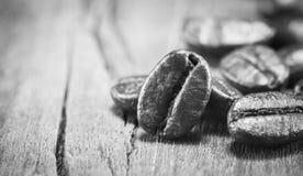 在黑白的咖啡豆纹理在木背景 库存图片
