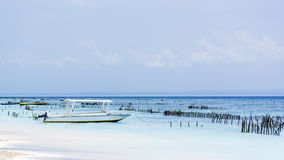 在水的一点小船在与蓝天的海滩在背景中 免版税库存照片