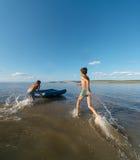 在水的两个男孩奔跑在airbed的可膨胀 库存照片