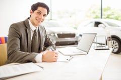 在他的书桌后的微笑的推销员 免版税库存图片