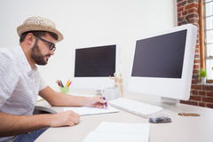 在他的书桌的偶然设计师图画 免版税库存照片