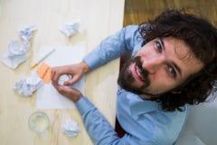 在他的书桌的图表设计师压皱纸 库存图片