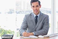 在他的书桌的微笑的商人文字 免版税库存图片