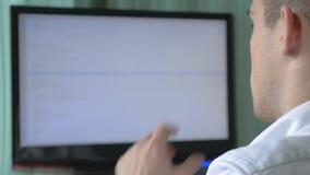 在他的书桌的年轻计算机程序设计者编制程序 股票视频