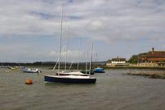 在他们的停泊的游船在历史的Bosham在英国的南部的西萨塞克斯郡怀有 库存照片