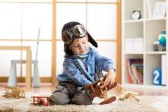 在他的儿童居室哄骗男孩与木玩具飞机的weared飞行员盔甲戏剧 免版税图库摄影