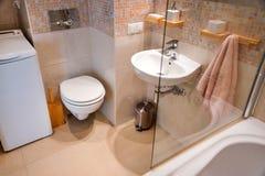 在轻的公寓的现代简单的内部 与玻璃门阵雨和镜子的卫生间内部 图库摄影