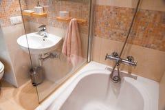 在轻的公寓的现代简单的内部 与玻璃门阵雨和镜子的卫生间内部 免版税库存照片