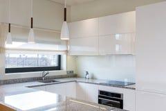 在轻的内部的现代厨房设计与木口音 库存照片