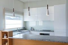 在轻的内部的现代厨房设计与木口音 图库摄影