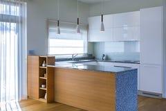 在轻的内部的现代厨房设计与木口音 免版税库存图片