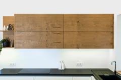 在轻的内部的现代厨房设计与木口音 免版税库存照片