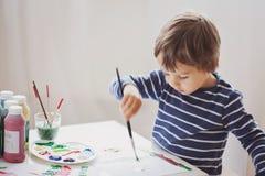 在他的册页的逗人喜爱的小男孩绘画 库存图片