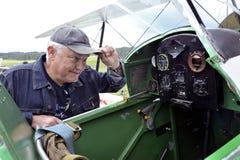 在他的双翼飞机前面的飞行员准备好起飞 免版税库存照片