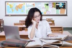 在类的可爱的女性学习者阅读书 免版税库存照片