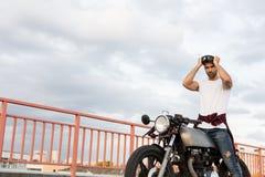在他的咖啡馆竟赛者风俗摩托车附近的残酷人 库存图片