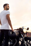 在他的咖啡馆竟赛者风俗摩托车附近的残酷人 图库摄影