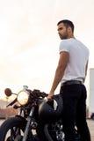 在他的咖啡馆竟赛者风俗摩托车附近的残酷人 库存照片