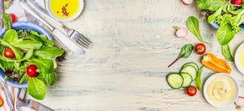 在轻的土气背景,顶视图,横幅的各种各样的绿色有机沙拉成份 免版税库存图片