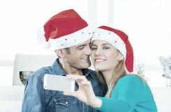 在他们的在家做圣诞节的30s的愉快的夫妇一selfie 免版税库存图片
